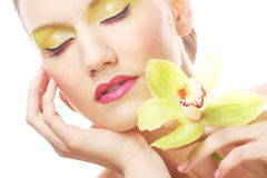 Junge Frau mit hellem bilden das Halten der Orchidee Stockfotos