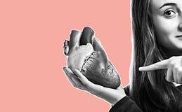Junge Frau mit Herzen in der Hand stockfotografie