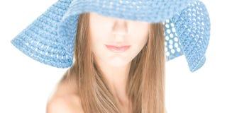 Junge Frau mit Hälfte verstecktem Gesicht unter blauem Hut. Stockfotos