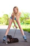 Junge Frau mit Hund auf Rollenrochen im Park Lizenzfreies Stockfoto
