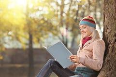 Junge Frau mit Hut ein Buch lesend und eine Sonne in einer Gleichheit genießend Stockfoto