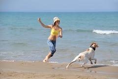 Junge Frau mit ihrem Hund auf dem Strand Lizenzfreie Stockfotografie