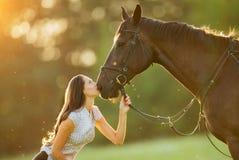 Junge Frau mit ihrem Pferd im Abendsonnenunterganglicht Stockfotografie
