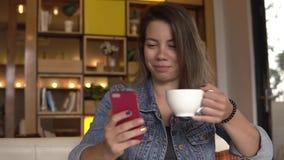 Junge Frau mit ihrem sitzenden und trinkenden Kaffee des Smartphone stock video