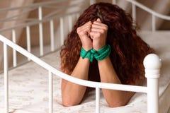 Junge Frau mit ihren Händen gebunden in der Knechtschaft lizenzfreie stockfotografie