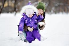 Junge Frau mit ihrer Tochter, die mit Schnee am Park spielt Lizenzfreies Stockbild