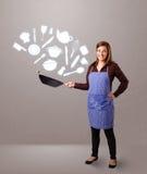 Junge Frau mit Küchenzubehörikonen Lizenzfreie Stockfotos