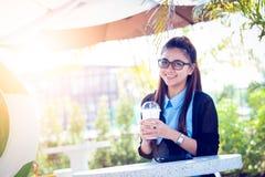 Junge Frau mit Kaffee im Garten Lizenzfreie Stockfotografie
