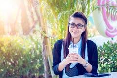 Junge Frau mit Kaffee im Garten Lizenzfreie Stockfotos