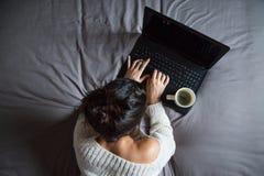 Junge Frau mit Kaffee und Laptop Stockfoto