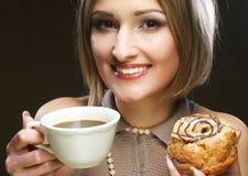 Junge Frau mit Kaffee und Plätzchen Stockbilder