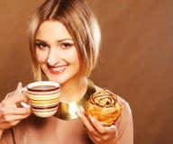 Junge Frau mit Kaffee und Plätzchen Stockfotos