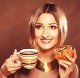 Junge Frau mit Kaffee und Plätzchen Lizenzfreie Stockfotos