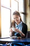 Junge Frau mit Kaffeetasse im Café Stockbilder