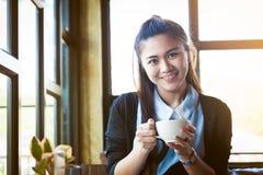 Junge Frau mit Kaffeetasse im Café Lizenzfreie Stockfotos