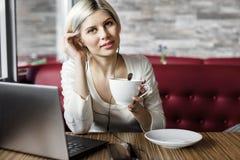 Junge Frau mit Kaffeetasse und Laptop im Café Stockfoto