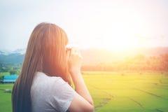 Junge Frau mit Kamerareisefoto des Fotografen auf den Gebieten Lizenzfreie Stockbilder