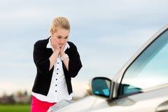 Junge Frau mit Karte auf dem Auto, das verloren ist Stockbilder
