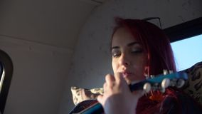Junge Frau mit Klammern auf den Zähnen, die Ukulelegitarre spielen stock video