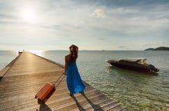 Junge Frau mit Koffer auf dem Pier Stockbild