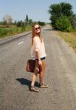 Junge Frau mit Koffer per Anhalter fahrend auf Straße in der Landschaft Lizenzfreies Stockfoto
