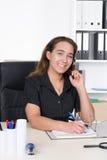 Junge Frau mit Kopfhörer schreibt in eine Datei Lizenzfreie Stockfotos