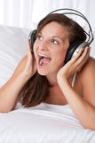 Junge Frau mit Kopfhörern singend Stockbilder