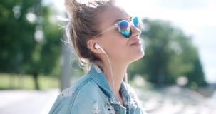 Junge Frau mit Kopfhörern Zeit in einer Stadt genießend Lizenzfreies Stockbild