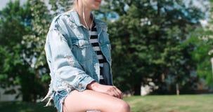 Junge Frau mit Kopfhörern Zeit in einer Stadt genießend Stockfotografie