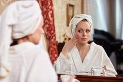 Junge Frau mit kosmetischer Sahne Lizenzfreie Stockfotos