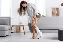 Junge Frau mit Krücke und dem gebrochenen Bein in der Form stockbilder