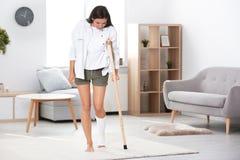 Junge Frau mit Krücke und dem gebrochenen Bein in der Form lizenzfreies stockfoto