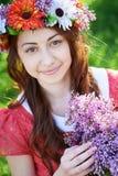 Junge Frau mit Kranz und mit lila Blumen im Frühjahr Lizenzfreies Stockfoto