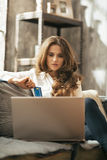 Junge Frau mit Kreditkarte unter Verwendung des Laptops im Dachboden Stockfotografie