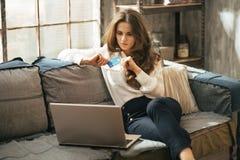 Junge Frau mit Kreditkarte unter Verwendung des Laptops im Dachboden Lizenzfreies Stockfoto