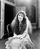 Junge Frau mit langen Locken, gelocktes Haar, gelocktes Sitzen auf einem Stuhl und Lächeln (alle dargestellten Personen sind nich Stockbilder