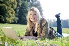 Junge Frau mit Laptop auf einer Wiese Lizenzfreie Stockbilder