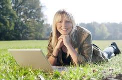 Junge Frau mit Laptop auf einer Wiese Stockbild