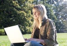 Junge Frau mit Laptop auf einer Wiese Lizenzfreie Stockfotografie
