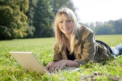Junge Frau mit Laptop auf einer Wiese Lizenzfreies Stockfoto