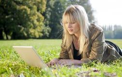 Junge Frau mit Laptop auf einer Wiese Stockbilder
