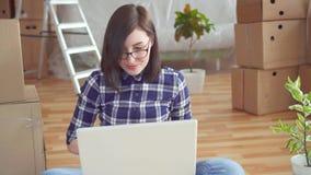 Junge Frau mit Laptop auf Hintergrund von Kästen und von Bauarbeiten stock footage