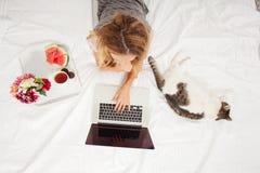 Junge Frau mit Laptop im Bett Stockfoto