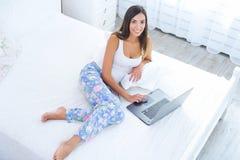 Junge Frau mit Laptop im Bett Lizenzfreie Stockbilder