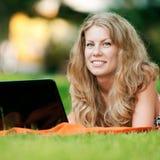 Junge Frau mit Laptop am Park Stockfoto