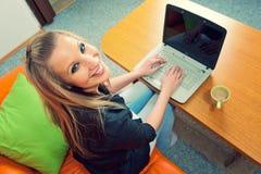 Junge Frau mit Laptop und Tasse Kaffee Stockfotos