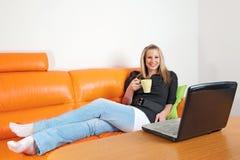 Junge Frau mit Laptop und Tasse Kaffee Stockfoto