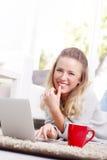 Junge Frau mit Laptop zu Hause Stockbild