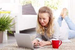 Junge Frau mit Laptop zu Hause Lizenzfreie Stockfotografie