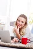 Junge Frau mit Laptop zu Hause Lizenzfreies Stockfoto